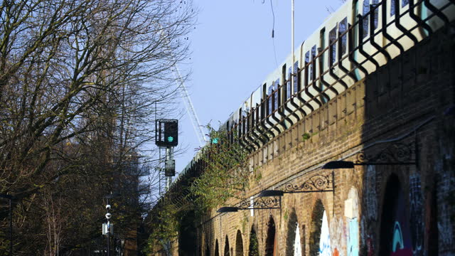 stockvideo's en b-roll-footage met commuter train over railway arches, london - sunny