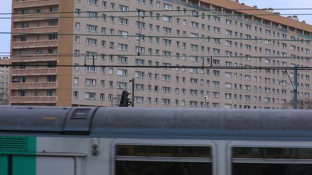 commuter train passes by social housing buildings on january 8, 2021 in nanterre, france. unlike the united kingdom or germany, the french government... - urban sprawl stock videos & royalty-free footage