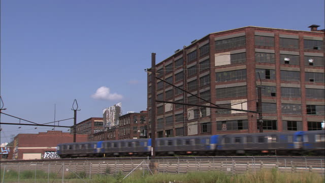 Commuter train passes in front of abandoned building