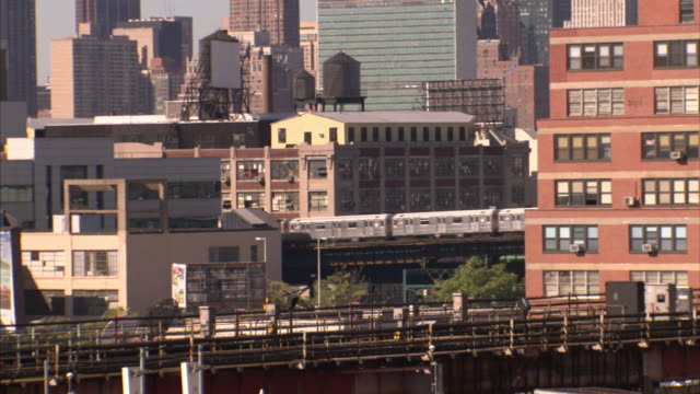 A commuter train passes industrial and residential buildings in New York City.