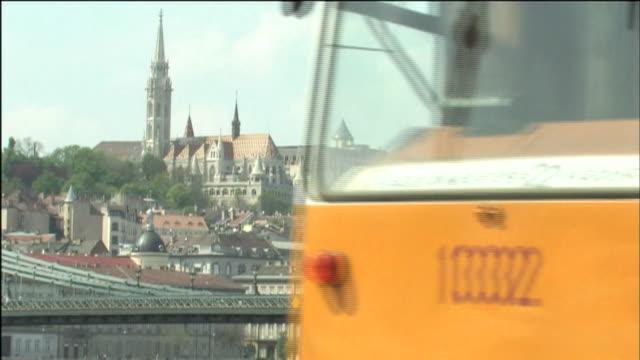 vidéos et rushes de a commuter train passes near a danube river bridge close to the hungarian parliament building. - budapest