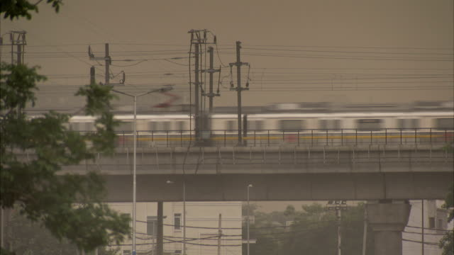 a commuter train speeds by on an overpass. available in hd. - bbc stock videos and b-roll footage