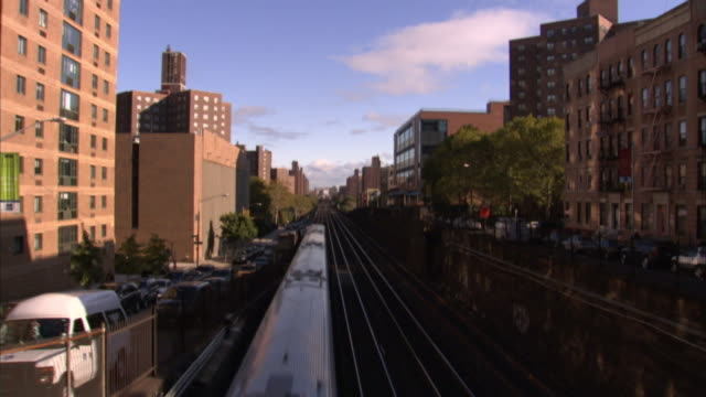 Commuter trains and traffic move through a neighborhood in New York City.