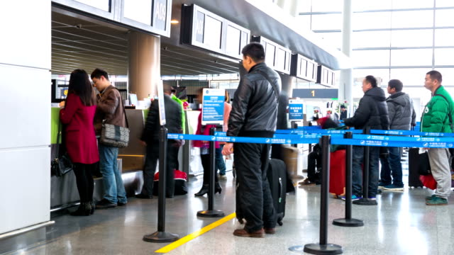 commuter traveler at airport departure terminal time lapse - airline check in attendant stock videos and b-roll footage