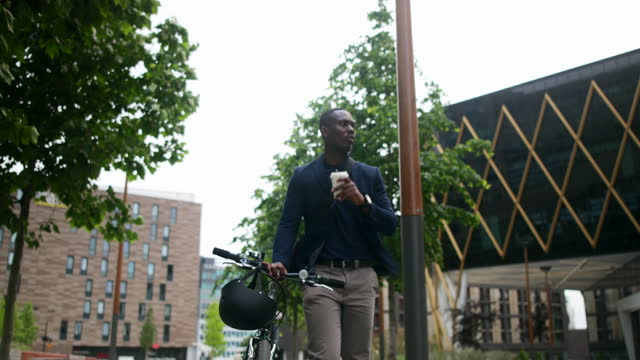 commuter walking with his bicycle & coffee - formal businesswear stock videos & royalty-free footage