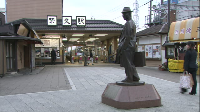 a commuter walks past the tora-san bronze statue in front of the shibamata station in tokyo. - shibamata stock videos & royalty-free footage
