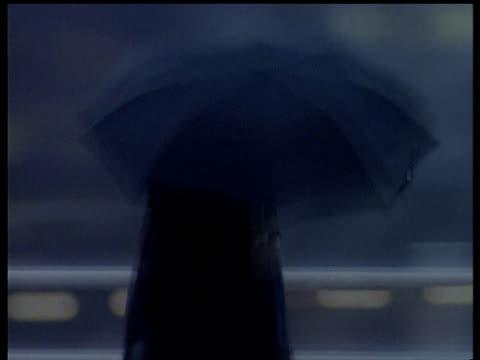 vídeos de stock, filmes e b-roll de commuter wearing raincoat walks over waterloo bridge in wet and windy weather with umbrella obscuring head london - capa de chuva