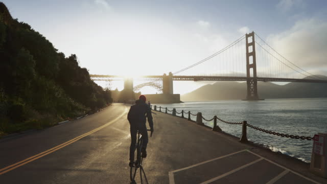 commuter with road racing bicycle and golden gate bridge - san francisco california video stock e b–roll