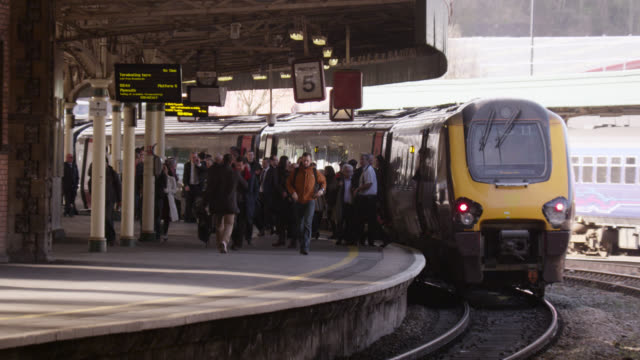 Commuters alight onto platform in Temple Meads train station, Bristol, England