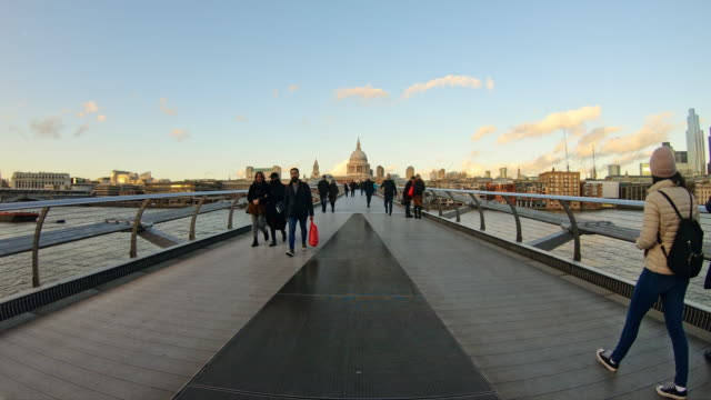 commuters and tourists on city footbridge at sunset - london millennium footbridge stock videos & royalty-free footage