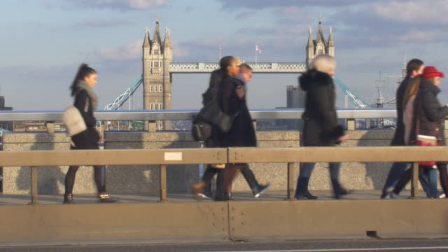 commuters and traffic crossing london bridge. - city life stock videos & royalty-free footage