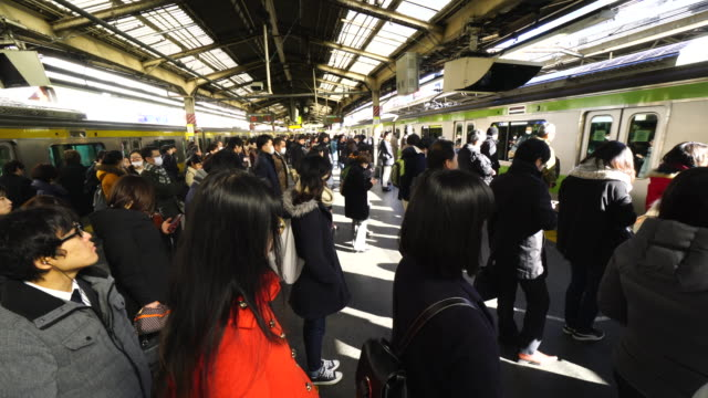 Commuters are waiting to get on to crowded Yamanote Line and passengers are getting out from the train.Scene of crowded morning commute at JR Shinjuku Station.