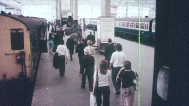 1976 MONTAGE Commuters at tram station, crossing a catwalk and walking along a congested city sidewalk / United Kingdom