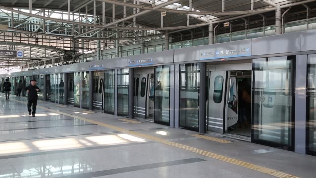stockvideo's en b-roll-footage met commuters board train at a subway station platform in incheon automatic doors of a subway train close for departure subway train departs station... - incheon