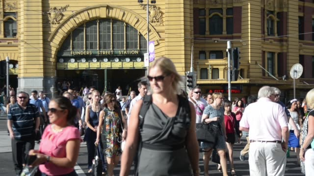 Commuters cross an intersection by the Flinders Street Station building in Melbourne Australia on Tuesday Feb 10 View of feet crossing an...