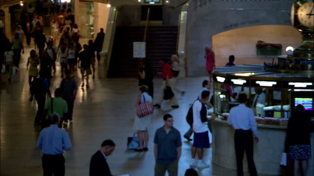 commuters cross the floor and buy tickets in new york city's grand central station. - grand central station manhattan stock videos & royalty-free footage