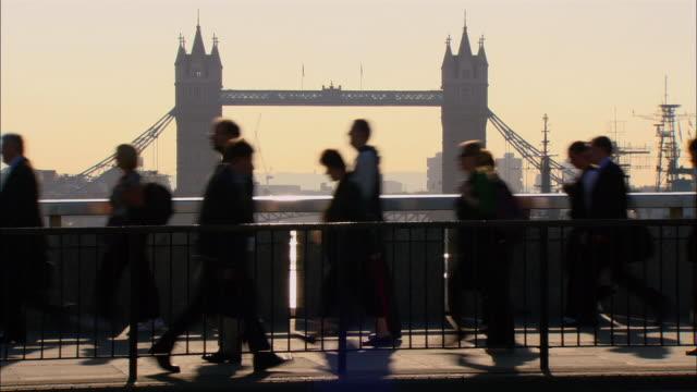 ms, commuters crossing london bridge, tower bridge in background, london, england - 2006 stock videos & royalty-free footage