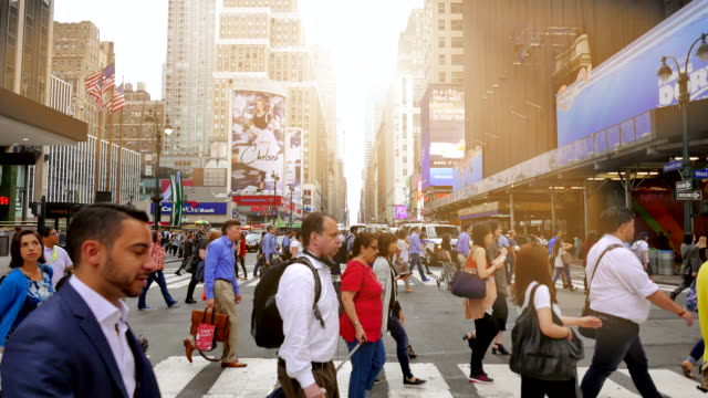 commuters crossing street in front of penn station in new york city going to work. pedestrians walking on crowded street - international landmark stock videos & royalty-free footage