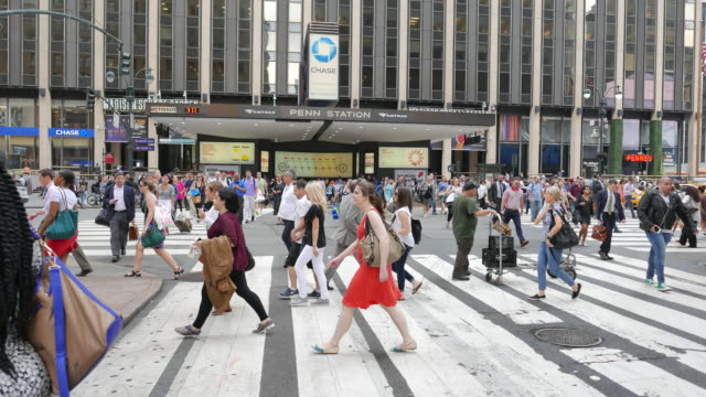 commuters crossing street in front of penn station in new york city going to work. pedestrians walking on crowded street - new york city penn station stock videos and b-roll footage
