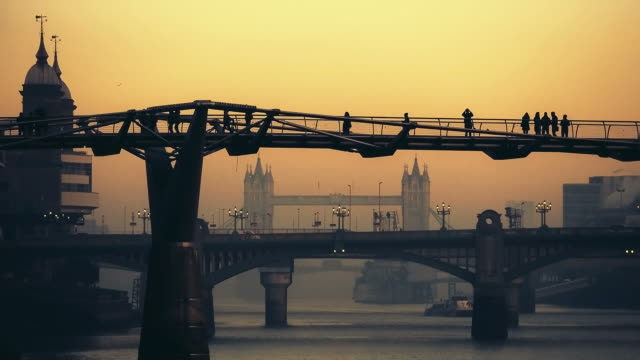 Commuters crossing the Millennium bridge with Tower Bridge at dusk