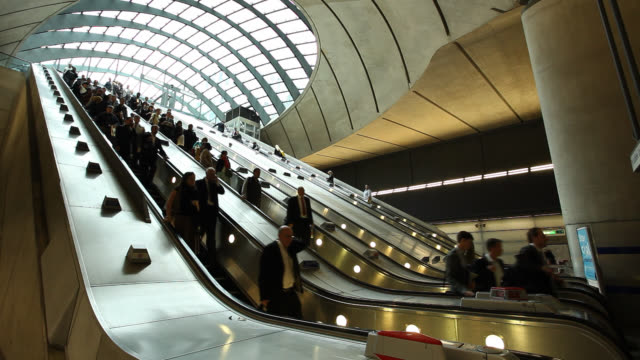 commuters descend a long, silver escalator inside london's canary wharf station. - escalator stock videos & royalty-free footage