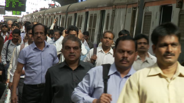 Commuters disembark from a train arriving at Churchgate Train Station.
