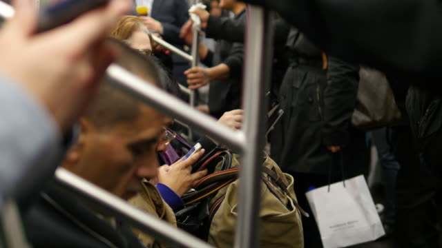 Commuters doing all kinds of things killing time during the ride in New York City using smart phone reading