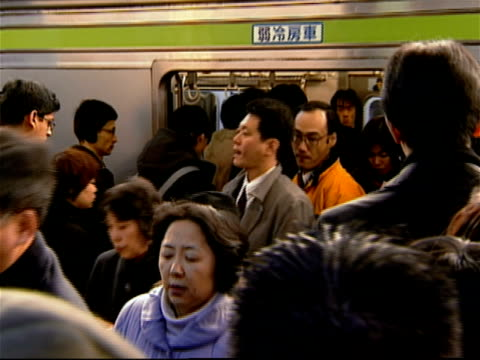stockvideo's en b-roll-footage met commuters entering and exiting subway train stopped at  shinjuku station at rush hour / tokyo, japan - metro spoorwegvervoer