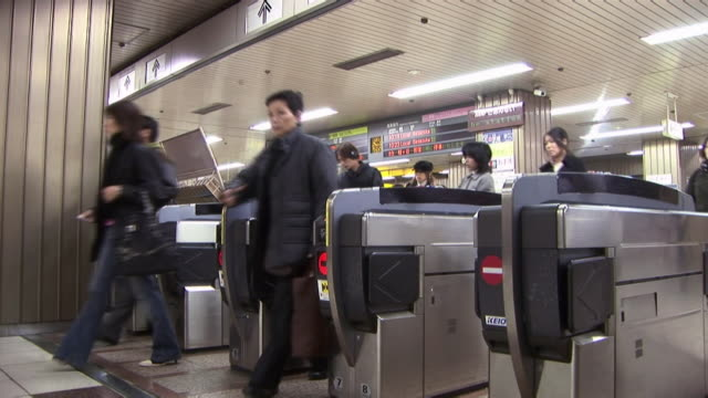 commuters exiting through turnstiles in subway station / tokyo - subway station stock videos & royalty-free footage