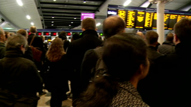 Commuters face disruption at London Bridge due to redevelopment work Various shots passengers on station concourse looking at departure boards at...