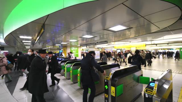 commuters go through the automatic ticket gates at jr shinjuku station. - 自動改札機点の映像素材/bロール