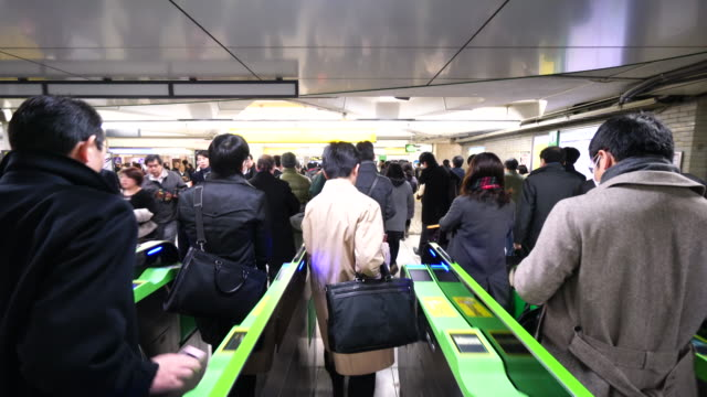 commuters go through the automatic ticket gates at jr shinjuku station. - routine stock videos & royalty-free footage