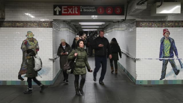Commuters head to a train as a police officer stands in a closedoff underground walkway near the site of a pipe bomb explosion in the tunnel that...