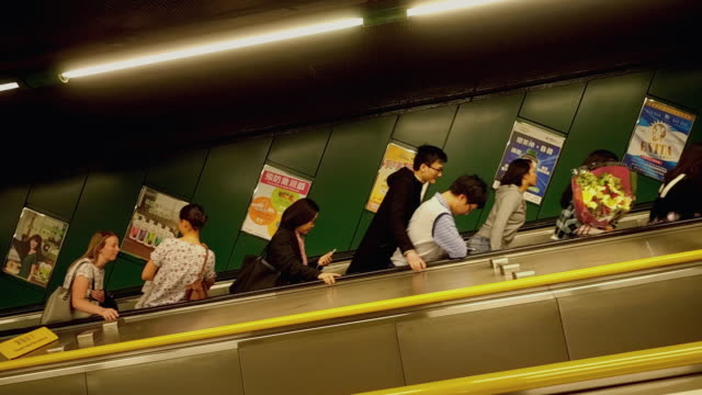 commuters heading up an escalator in an underground subway, hong kong island, hong kong - poster stock-videos und b-roll-filmmaterial