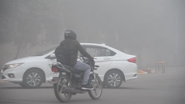 commuters in a road, amid dense fog, on a cold winter morning in new delhi, january. 1, 2021. delhi recorded the season's lowest temperature at 1.1... - luftförorening bildbanksvideor och videomaterial från bakom kulisserna