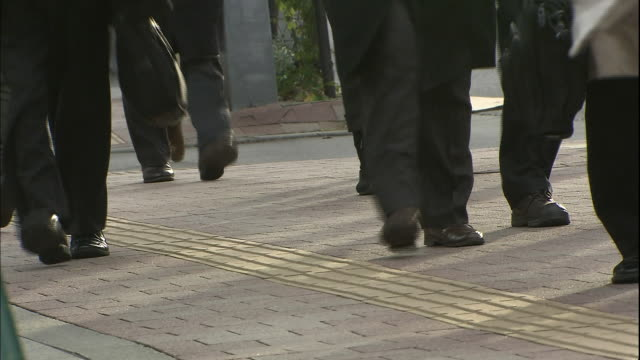 Commuters in business suits walk on a sidewalk.