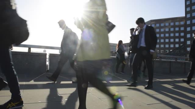 Commuters in London walking backlit by sun