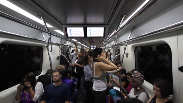 commuters in the crowded subway swinging and people holding as a young woman makeup her eye on the mobile screen. no audio - commercial land vehicle stock videos & royalty-free footage