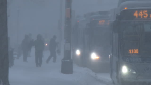 Commuters in Waterbury Connecticut get on and off of city buses during the morning rush hour in very heavy snow and near whiteout conditions during...