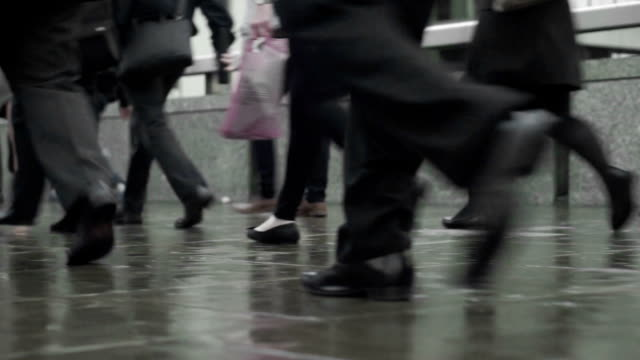Commuters legs on a rainy street, looped video  COM