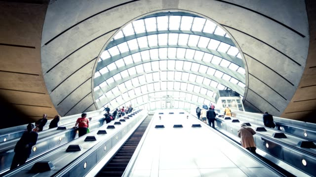 commuters on escalator at subway station canary wharf, docklands london - futuristic stock videos & royalty-free footage