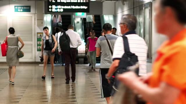 Commuters on escalators, at Singapore metro station.