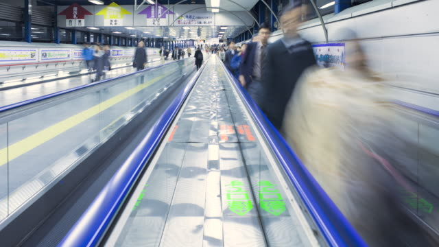 MS T/L Commuters on moving walkway in  Shibuya Station at rush hour / Tokyo, Japan