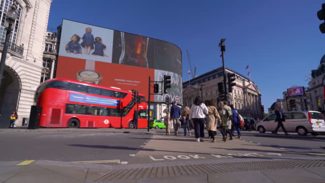 commuters on the crossing during morning rush hour traffic in piccadilly circus in london. - advertisement stock videos & royalty-free footage