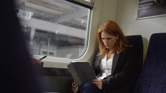 commuters on the their way to work using technology - bahnreisender stock-videos und b-roll-filmmaterial