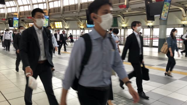 commuters pass through shinagawa train station the day after japans state of emergency was fully lifted from the coronavirus pandemic on may 26, 2020... - japan stock videos & royalty-free footage