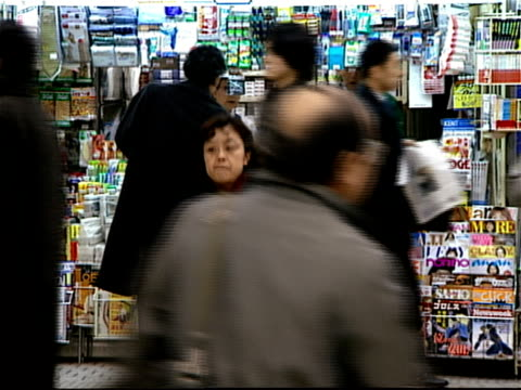 commuters purchasing newspapers from vendors at news stand inside shinjuku station at rush hour / one man wearing  mask to prevent spread of illness / tokyo, japan - 保護マスク点の映像素材/bロール