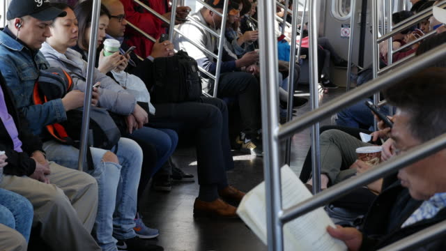 Commuters reading, drinking and using smart phone on New York City subway train