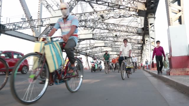 commuters ride their bicycles past the landmark howrah bridge over ganga river on world bicycle day on june 3, 2020 in kolkata, india. - howrah bridge stock videos & royalty-free footage