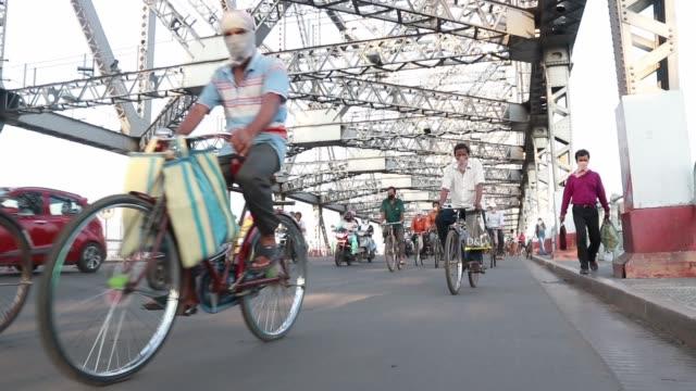 commuters ride their bicycles past the landmark howrah bridge over ganga river on world bicycle day on june 3, 2020 in kolkata, india. - kantilever bildbanksvideor och videomaterial från bakom kulisserna